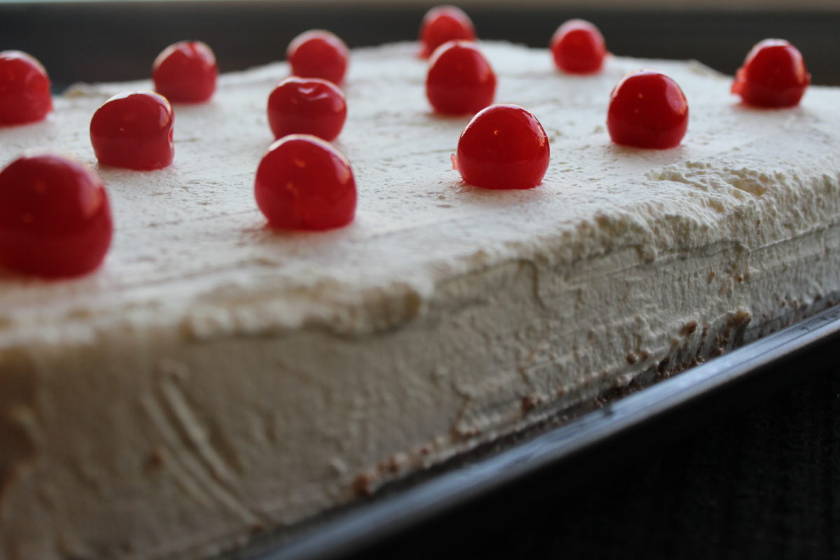 This Tres Leches Cake is soaked in three different kinds of milk and topped with freshly made cream and a cherry.